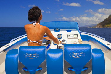 DOM0080AW Dominica, Soufriere. A young woman at the helm of a  Powerboat near Soufriere. (MR).