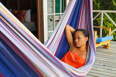 DOM0088AW Dominica, Delices. A young lady relaxes in a hammock at Jungle Bay Resort and Spa. (MR). (PR).