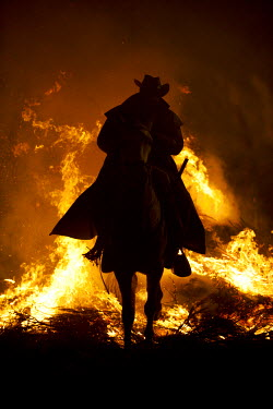 SPA4994 Spain, Castille & Leon, Avila, San Bartolome de Pinares, Men and horses jumping through fire on the eve of the feast of San Antonio, as a tradition to purify the animals.