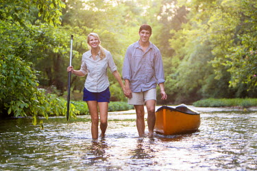 AR4776700003 Helena, Alabama, USA : A young man and a young woman hold hands as they walk their canoe upstream laughing.