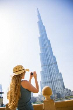UE01489 Woman photographing the Burj Khalifa in Downtown, Dubai, United Arab Emirates (MR)