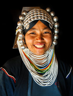 A woman from Akha tribal village wearing traditional headdress made of heavy silver baubles and beads sewn on a bamboo cap, near Kyaing Tong, Shan State, Burma/ Myanmar