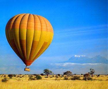 KEN8071 Kenya, Voi County, Maktau, Tsavo West National Park.  A hot air balloon rises in sight of Mount Kilimanjaro.