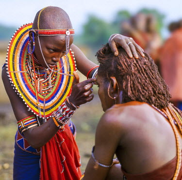KEN8094 Kenya, Kilgoris County, Oloololo.  A Maasai girl decorates the face of her warrior boyfriend during an eunoto ceremony.