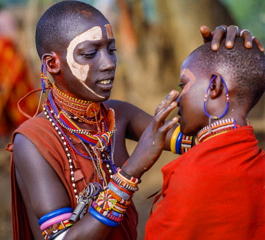 KEN8095 Kenya, Kilgoris County, Oloololo.  A Maasai girl decorates the face of her friend during an eunoto ceremony.