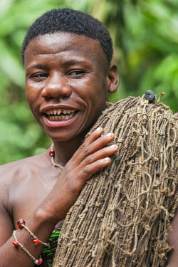 CAR0018 Central African Republic, Bayanga.  A Ba�Aka woman with facial tattoos and filed teeth carries her hunting net into the rainforest.