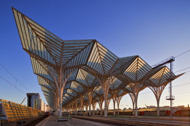 POR7064 Contemporary modern steel and glass railway platform canopy of the Oriente Railway station, designed by the the architect / engineer Santiago Calatrava Valls at sunset in Olivais, Lisbon, Lisboa, Port...
