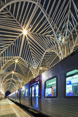 POR7068 Contemporary modern modern steel and glass railway platform canopy of the Oriente Railway station, designed by the the architect / engineer Santiago Calatrava Valls at twilight with a Comboios de Port...
