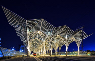 POR7069 Contemporary modern modern steel and glass railway platform canopy of the Oriente Railway station, designed by the the architect / engineer Santiago Calatrava Valls at twilight with a Comboios de Port...