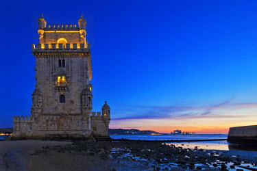 POR7080 The early 16th century Portuguese Manueline Style, Torre de Belem designed by the architect Francisco de Arruda at twilight with the River Tagus Estuary in the background, in Pedroucos, Belem, Cruz Qu...
