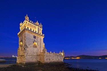 POR7081 The early 16th century Portuguese Manueline Style, Torre de Belem designed by the architect Francisco de Arruda at twilight with the River Tagus Estuary in the background, in Pedroucos, Belem, Cruz Qu...