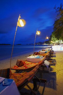 Tables set for dinner at Amari Palm Reef on Chaweng beach at dusk, Ko Samui, Thailand
