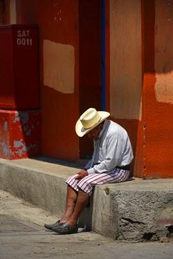 GUA1099AW Man sat in the street in Santiago Atitlanl, Guatemala, Central America