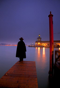 Italy, Veneto, Venice, Man in tabarro, the typical Venetian cloak, overlooking the Gran Canal and the Punta della Dogana. MR