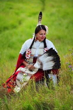 USA8668AW Lakota Woman in full regalia sitting in meadow at Lakota Lake, Custer County, Black Hills National Forest, Western South Dakota, USA. MR