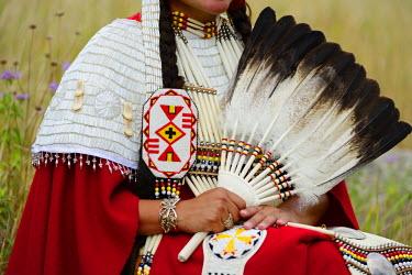 USA8677AW Lakota Woman in full regalia sitting in meadow at Lakota Lake, Custer County, Black Hills National Forest, Western South Dakota, USA. MR
