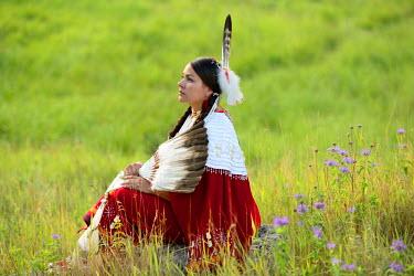 USA8678AW Lakota Woman in full regalia sitting in meadow at Lakota Lake, Custer County, Black Hills National Forest, Western South Dakota, USA. MR