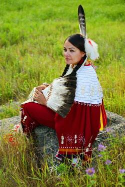 USA8679AW Lakota Woman in full regalia sitting in meadow at Lakota Lake, Custer County, Black Hills National Forest, Western South Dakota, USA. MR