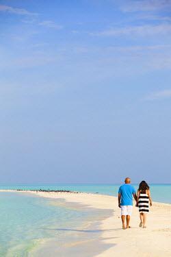 MIV0071AW Maldives, Rasdhoo Atoll, Kuramathi Island. A couple walk along the sandbank at Kuramathi Island Resort. MR.