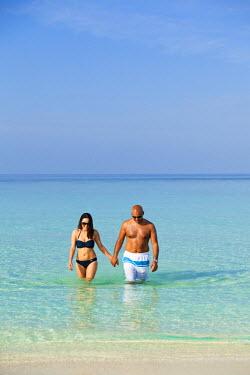 MIV0072AW Maldives, Rasdhoo Atoll, Kuramathi Island. A couple walk out of the sea at Kuramathi Island Resort. MR.