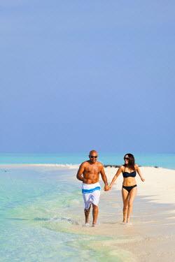 MIV0073AW Maldives, Rasdhoo Atoll, Kuramathi Island. A couple run along the sandbank at Kuramathi Island Resort. MR.