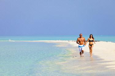 MIV0074AW Maldives, Rasdhoo Atoll, Kuramathi Island. A couple run along the sandbank at Kuramathi Island Resort. MR.