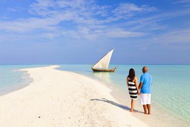 MIV0075AW Maldives, Rasdhoo Atoll, Kuramathi Island. A couple on honeymoon stand looking at a traditional Maldivian Dhow on the sandbank at Kuramathi Island Resort. MR.