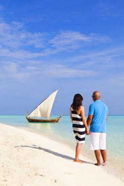 MIV0076AW Maldives, Rasdhoo Atoll, Kuramathi Island. A couple on honeymoon stand looking at a traditional Maldivian Dhow on the sandbank at Kuramathi Island Resort. MR.
