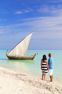 MIV0077AW Maldives, Rasdhoo Atoll, Kuramathi Island. A couple on honeymoon stand looking at a traditional Maldivian Dhow on the sandbank at Kuramathi Island Resort. MR.