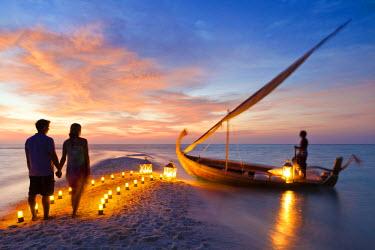 MIV0091AW Maldives, Rasdhoo Atoll, Kuramathi Island. A couple wait to board a traditional Dhoni on the sandbank at Kuramathi Island Resort. MR.