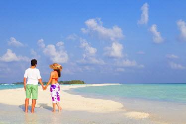 MIV0108AW Maldives, Rasdhoo Atoll, Kuramathi Island. A couple on honeymoon stand on the sandbank at Kuramathi Island Resort. MR.