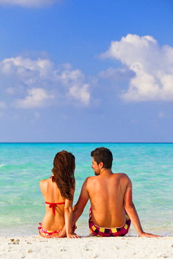 MIV0110AW Maldives, Rasdhoo Atoll, Kuramathi Island. A couple on honeymoon sit looking out to sea at Kuramathi Island Resort. MR.