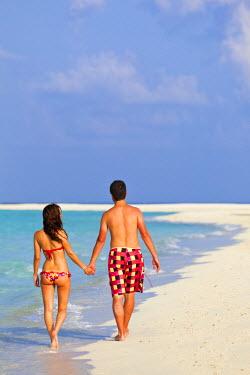 MIV0112AW Maldives, Rasdhoo Atoll, Kuramathi Island. A couple walk along the sandbank at Kuramathi Island Resort. MR.