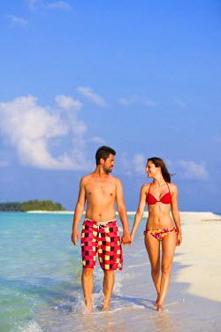 MIV0113AW Maldives, Rasdhoo Atoll, Kuramathi Island. A couple walk along the sandbank at Kuramathi Island Resort. MR.