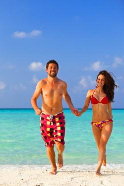 MIV0114AW Maldives, Rasdhoo Atoll, Kuramathi Island. A couple on honeymoon run out of the sea at Kuramathi Island Resort. MR.