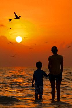 MIV0122AW Maldives, Rasdhoo Atoll, Kuramathi Island. A mother and sun watch the sun setting. MR.