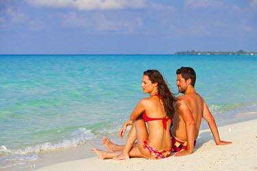 MIV0111AW Maldives, Rasdhoo Atoll, Kuramathi Island. A couple on honeymoon sit looking out to sea at Kuramathi Island Resort. MR.