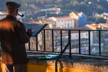 POR7195 Man painting in Alfama district, Lisbon, Portugal, Europe