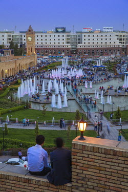 IQ01028 Iraq, Kurdistan, Erbil, Men sitting on walls at Citadel looking over Shar park (City Center Park) and Qaysari Bazaars