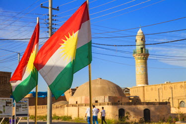 IQ01032 Iraq, Kurdistan, Erbil, The Citadel, Men walking past mosque and Kurdish flag
