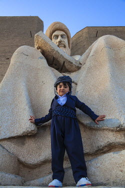 IQ01075 Iraq, Kurdistan, Erbil, Boy standing by Statue of Mubarak Ben Ahmed Sharaf-Aldin at the main entrance to The Citadel