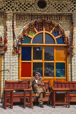 IQ01083 Iraq, Kurdistan, Erbil, Qaysari Bazaar, Man sitting outside tea shop at base of The Citadel