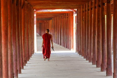 BM01287 Monk in walkway of wooden pillars to temple, Salay, Myanmar, (Burma)