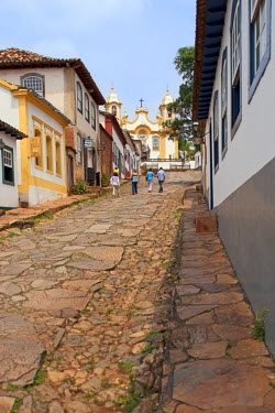BRA1927AW South America, Brazil, Minas Gerais state, Tiradentes, view of colonial houses and the Matriz de Santo Antonio church from along a cobbled street in the town centre
