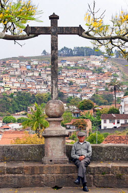 BRA1945AW South America, Brazil, Minas Gerais state, Ouro Preto, an old man sitting next to a cross in the town centre