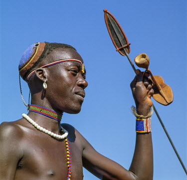 Kenya, Nginyang, Baringo County. A Pokot warrior wearing a traditional, distinctive clay bun hairstyle with his spear and wooden stool in hand.
