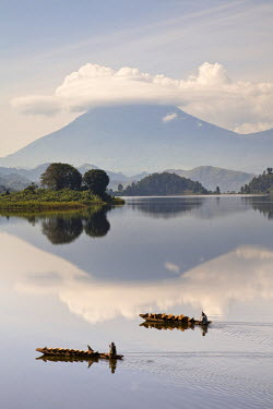 AF48MZW0240 Dugout canoe floating on Lake Mutanda with the Virunga Volcanoes in the background. Kisoro, Kigezi, Uganda.