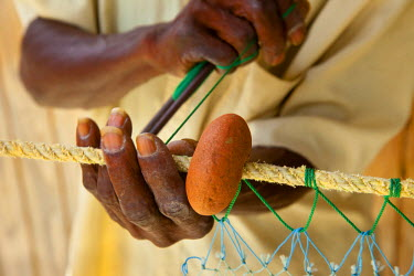 CA33BJN0007 Weathered hands of old fisherman mending nets in Canaries, St. Lucia, West Indies.