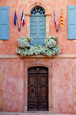 EU09BJN0528 Balcony, flowers and flags, Roussillon, Vaucluse. Provence, France.