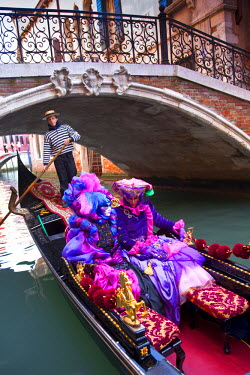 EU16BJY0043 Europe, Italy, Venice. Man and Woman women in gondola dressed in elaborate costume for Carnival festival.